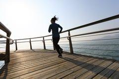 Female jogger morning exercise on seaside boardwalk during sunrise Stock Photography
