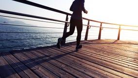 Female jogger morning exercise on seaside boardwalk during sunrise Royalty Free Stock Images