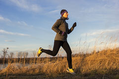 Female jogger in the morning. Female young adult running in the morning by the lake stock photo