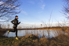 Female jogger in the morning. Female young adult running in the morning by the lake stock images