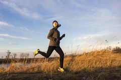Female jogger in the morning. Female young adult running in the morning by the lake stock image