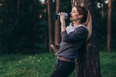 Female jogger recovering after intensive workout standing near the tree drinking water, wearing headphones in park.  stock photography