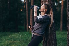 Female jogger recovering after intensive workout standing near the tree drinking water, wearing headphones in park.  royalty free stock photography