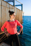 Female jogger resting after morning run along seashore while standing by the sea in sunny summer day Royalty Free Stock Photography