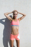 Female jogger resting after workout outdoors. Half length portrait of tired fit woman dressed in sport bra and shorts taking break after physical activity royalty free stock images