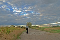 Female jogger. Runnig cross country under the cloudy sky Royalty Free Stock Images