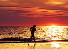 Female jogger running on beach at sunset. Royalty Free Stock Photo