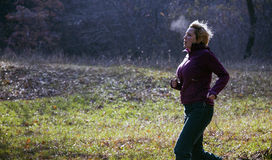 Female jogger running at cold morning rising breath vapour Stock Image