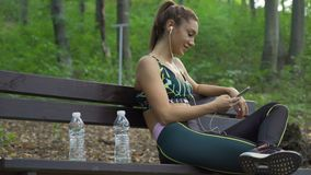 Female jogger with trail running shoes and sportswear relaxing on a bench, listening music. Water bottles next to a. Beautiful fitness girl using mobile phone stock video