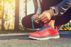 Female jogger tying her shoes outside Royalty Free Stock Photo
