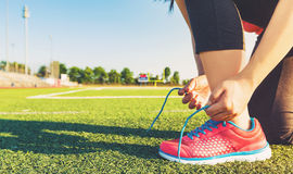 Female jogger tying her shoes on a stadium field Royalty Free Stock Photo