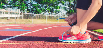 Female jogger tying her shoes on a stadium track Royalty Free Stock Image
