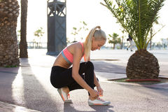 Female jogger tying shoelaces on her running shoes during fitness training in urban setting royalty free stock images