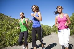 Female Joggers running together outdoors. Three Female Joggers running together outdoors Royalty Free Stock Images