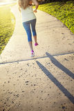 Female jogging in a city park view from behind Stock Photography