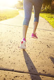 Female jogging in a city park view from behind Royalty Free Stock Photography