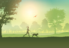 Female jogging with dog in countryside Stock Photo
