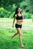 Female jogging outside in the park. Royalty Free Stock Photography