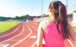 Female jogging on at a stadium track Royalty Free Stock Image