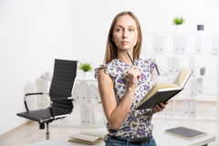 Female with journal. Female standing at office desk with journal in hands Royalty Free Stock Images