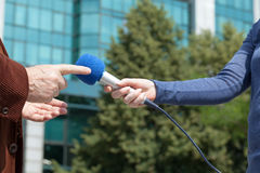 Female journalist conducting an interview with businessman or politician Stock Photos