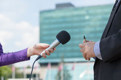Female journalist interviewing businessman, corporate building in background Stock Photos