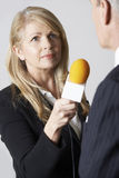 Female Journalist With Microphone Interviewing Businessman. Journalist With Microphone Interviewing Businessman Stock Photography