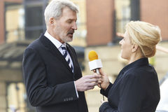 Female Journalist With Microphone Interviewing Businessman. In Street Royalty Free Stock Photo