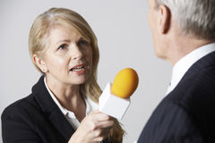 Female Journalist With Microphone Interviewing Businessman. In Studio Royalty Free Stock Photos