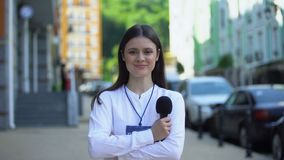 Female journalist with microphone and press pass looking at camera on street