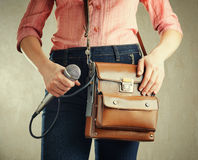 Female journalist with microphone. Retro style jeans and bag Stock Photo