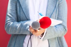 Female journalist at news conference, writing notes, holding mic Stock Photos