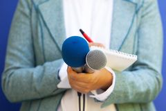 Female journalist at news conference, writing notes, holding microphone stock photography