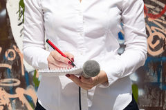Female journalist at news event, writing notes, holding microphone Royalty Free Stock Photos