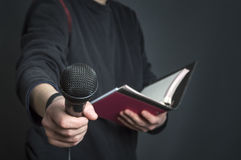 Female journalist at press conference holding microphone and notes. Selective focus stock photography