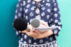 Female journalist or reporter at press conference, taking notes, holding microphones Royalty Free Stock Photos