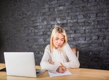 Young woman candidate writing on a summary, sitting at the table with laptop computer. Female journalist working with paper documents and portable net-book Stock Photo