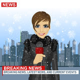 Female journalist working in winter in front of city with skyscrapers holding microphone Royalty Free Stock Photo