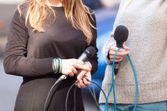Female journalists holding microphones waiting for press conference stock photo