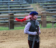 Female Jousting Assistant MD Renaissance Festival. A young woman, dressed in medieval costume, assists the horsemen in the jousting arena by holding swords at Royalty Free Stock Images