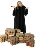 Female Judge and 70 Year Old Law Books. Pretty blonde woman judge in black robe with gavel standing behind stack of 70 year old law books Royalty Free Stock Images