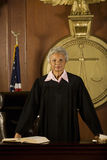 Female Judge Standing In Court Room. Portrait of confident senior female judge standing in court room royalty free stock photos