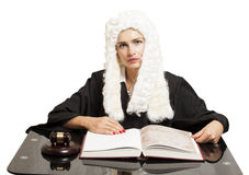 Female judge wearing a wig and black mantle with judge gavel and Stock Photography