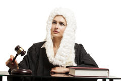 Female judge wearing a wig and black mantle with judge gavel and Royalty Free Stock Photos