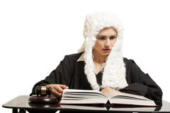 Female judge wearing a wig and black mantle with  judge gavel an Royalty Free Stock Image
