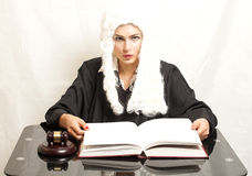 Female judge wearing a wig and black mantle with  judge gavel an Royalty Free Stock Photo