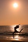 Female jumping at beach. On sunrise Stock Photos