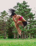 Female jumping outside in the park.  Royalty Free Stock Photo