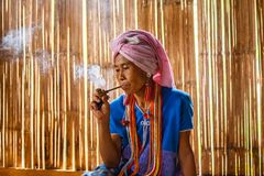 Female karen hill tribe is smoking tobacco pipe traditional in the cottage of northern Thailand at Mae Klang Luang. Mae Chaem, Chiang Mai Province Royalty Free Stock Photos