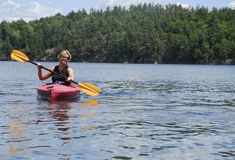 A Female Kayaks Calm Water Stock Photo